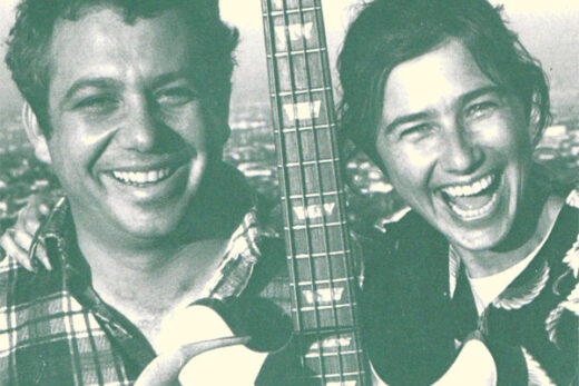 Mike Watt and Kira smiling with bass guitar in hand