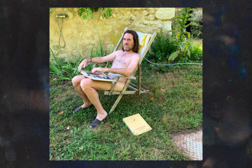 shows album cover: black border with naked man seated in field, reading